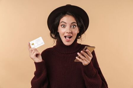 Image of shocked young brunette woman posing isolated over beige wall background holding credit card using mobile phone. 版權商用圖片