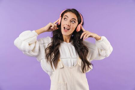 Photo of happy cheery brunette woman posing isolated over purple wall background listening music with headphones.