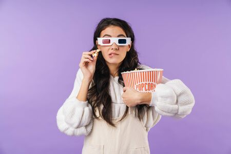 Photo of nervous brunette woman posing isolated over purple wall background watch tv cinema in 3d glsases eat popcorn bite lip.