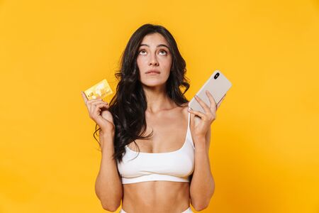 Image of thinking woman in swimsuit holding credit card and cellphone isolated over yellow wall 스톡 콘텐츠