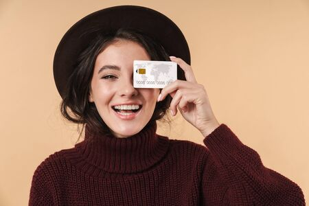 Image of cheery positive young brunette woman posing isolated over beige wall background holding credit card.
