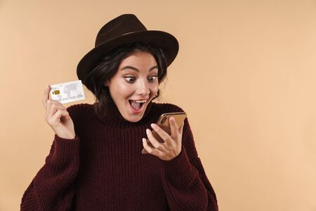 Image of screaming happy positive young brunette woman posing isolated over beige wall background holding credit card using mobile phone.