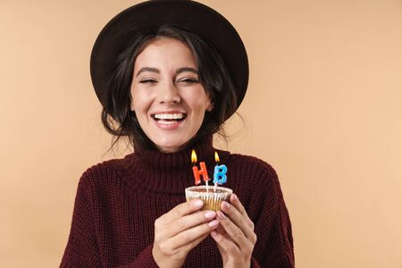 Photo of young cheerful happy brunette woman isolated over beige wall background holding cupcake with happy birthday candles. 版權商用圖片