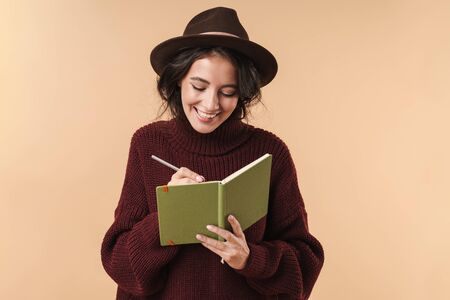 Photo of young cheery positive brunette woman isolated over beige wall background writing notes in notebook.