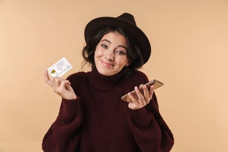 Image of confused unsured young brunette woman posing isolated over beige wall background holding credit card using mobile phone. 스톡 콘텐츠