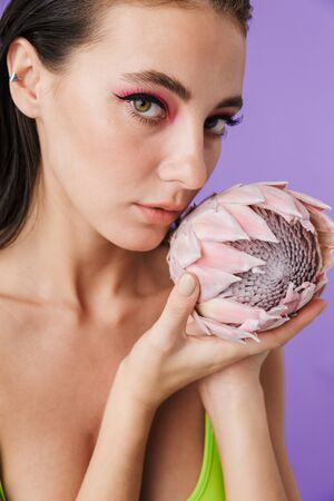 Photo closeup of attractive brunette woman with bright makeup holding exotic flower isolated over violet background 版權商用圖片