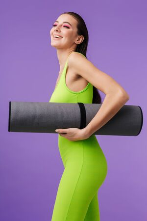 Photo of sporty happy woman with bright makeup holding yoga mat and smiling isolated over violet background