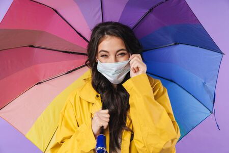 Image of positive happy woman in yellow raincoat posing isolated over purple wall background holding umbrella wearing medical mask.