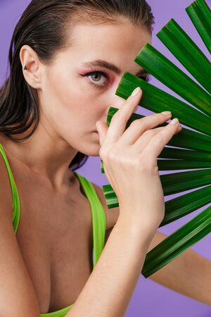 Photo closeup of nice seductive woman with bright makeup holding palm leaf isolated over violet background 版權商用圖片