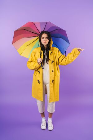Photo of cute sad brunette woman in yellow raincoat posing isolated over purple wall background holding umbrella.