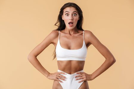 Image of a beautiful shocked surprised young woman in swimwear posing isolated over beige wall background.