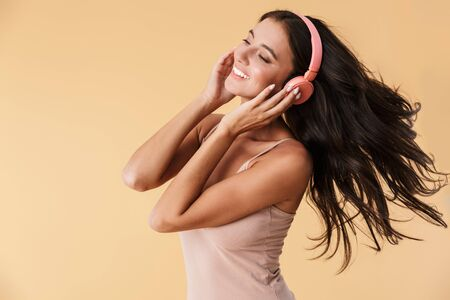 Image of a happy woman in headphones listening music posing isolated over beige wall background.
