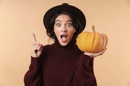 Image of young shocked surprised brunette woman isolated over beige wall background holding pumpkin pointing have an idea.