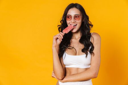 Image of attractive nice woman in swimsuit and eyeglasses eating ice cream isolated over yellow wall