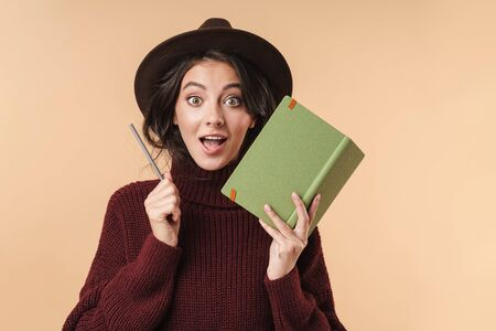 Photo of young surprised brunette woman isolated over beige wall background writing notes in notebook.