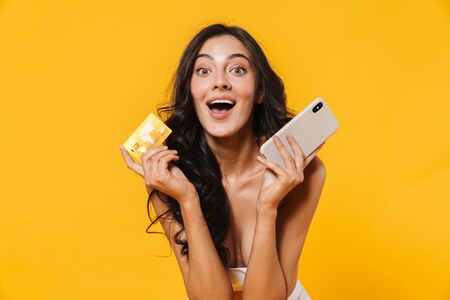 Image of excited woman in swimsuit holding credit card and cellphone isolated over yellow wall