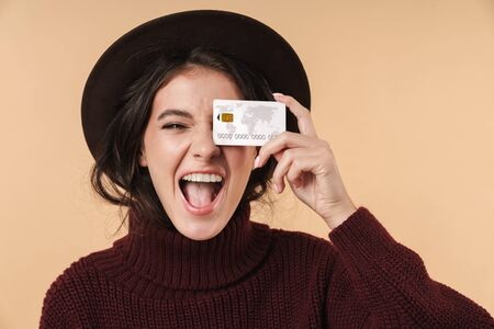 Image of happy emotional young brunette woman posing isolated over beige wall background holding credit card.