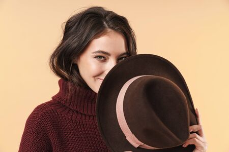 Image of cute positive young brunette woman posing isolated over beige wall background covering face with hat. 版權商用圖片