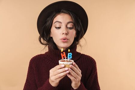 Photo of young beautiful brunette woman isolated over beige wall background holding cupcake blowing out happy birthday candles.