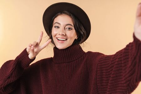 Image of positive optimistic young brunette woman posing isolated over beige wall background take a selfie by camera showing peace gesture. 版權商用圖片