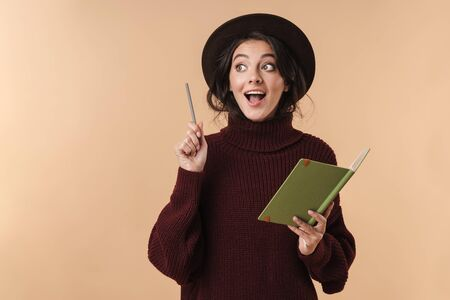 Photo of young surprised brunette woman isolated over beige wall background writing notes in notebook have an idea.