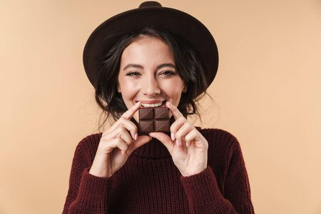 Photo of young cheerful happy pretty woman isolated over beige wall background holding chocolate.