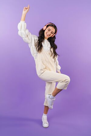 Photo of positive optimistic cheery brunette woman posing isolated over purple wall background listening music with headphones dancing.