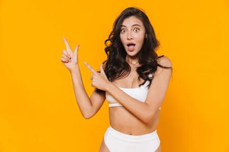 Image of young surprised woman in swimsuit pointing fingers aside isolated over yellow wall