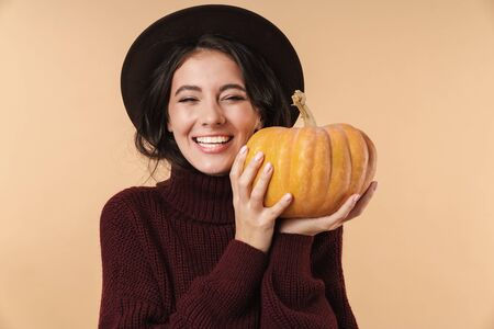 Image of young happy cheery brunette woman isolated over beige wall background holding pumpkin.