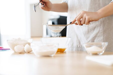 Cropped image of caucasian young woman preparing dough while cooking pie in modern kitchen Archivio Fotografico
