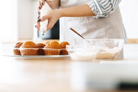 Cropped image of young caucasian woman wearing apron cooking muffins with cream in modern kitchen