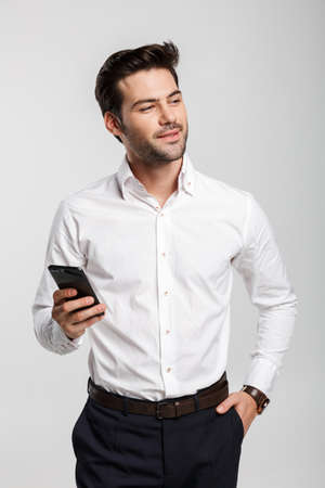 Image of young serious businessman holding and using laptop isolated over white background