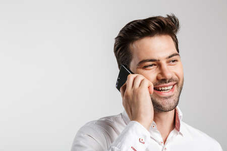 Image of young laughing man using earphones and holding water bottle while working out isolated over white background