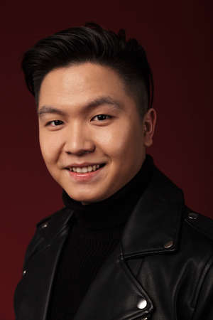 Image of joyful asian man in leather jacket smiling and looking at camera isolated over burgundy background