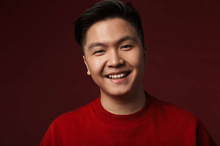 Image of happy young asian man smiling and looking at camera isolated over burgundy background Banque d'images