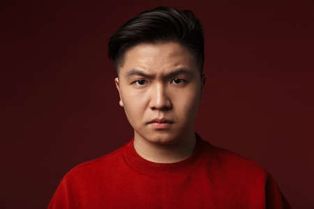 Image of displeased young asian man posing and looking at camera isolated over burgundy background Imagens