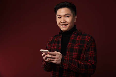 Image of cheerful asian man smiling and using mobile phone isolated over burgundy background