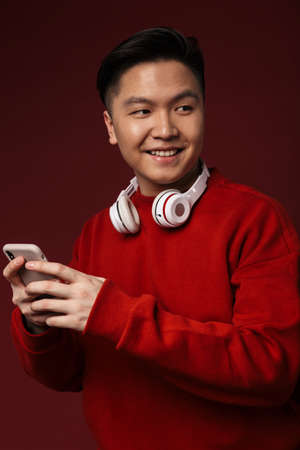 Image of joyful young asian man smiling while using headphones and cellphone isolated over burgundy background Banque d'images