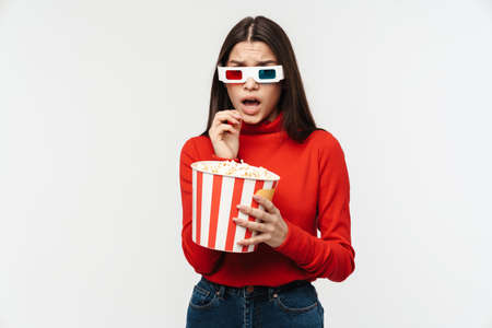 Photo of uptight brunette woman wearing 3D glasses holding popcorn bucket isolated over white background