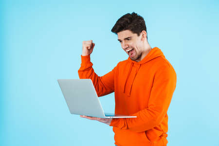 Image of excited young bristle man isolated over blue wall background using laptop computer while making winner gesture.