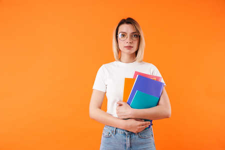 Portrait of lovely excited young blonde woman wearing casual clothes standing isolated over orange background, holding folders
