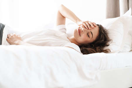 Photo of pretty brunette beautiful woman in basic t-shirt lying on bed after sleep or nap Banque d'images