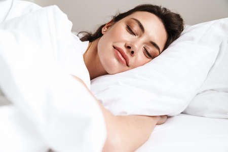 Photo of pretty beautiful woman with curly hair wearing basic t-shirt sleeping in bed at home