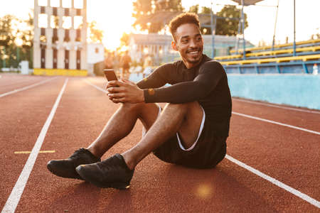 Image of joyful african american man holding smartphone while sitting at sports ground outdoors