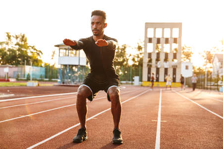 Image of brunette african american man doing workout at sports ground outdoors Zdjęcie Seryjne