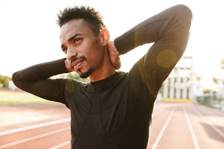 Image of serious african american man in sportswear touching his neck while doing workout at stadium in morning outdoors