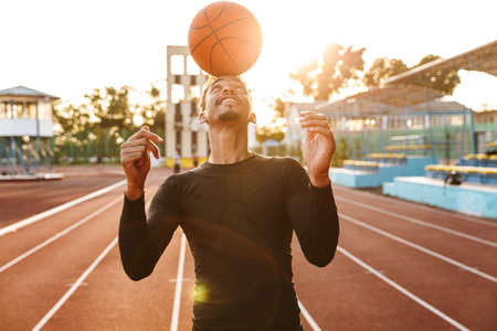 Photo of african strong positive young sports man at stadium outdoors play basketball.