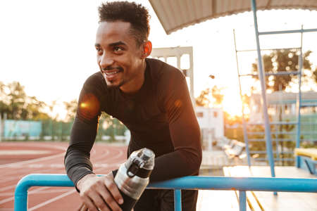 Image of happy african american man in sportswear holding water bottle while standing by railing at stadium outdoors