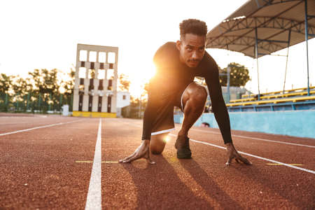 Image of concentrated african american man getting ready to start running on sports stadium outdoors