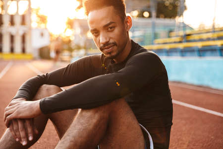 Image of handsome african american man sitting at sports ground while doing workout outdoors Zdjęcie Seryjne